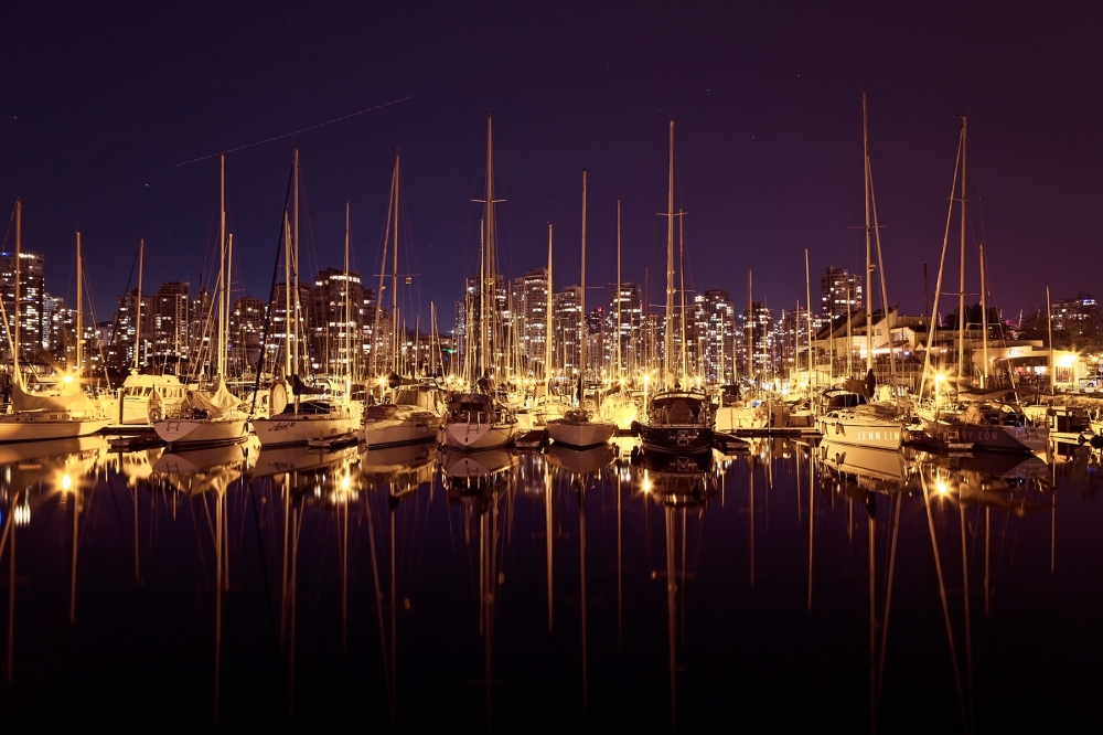 Boats docked along False Creek at night in Vancouver, BC