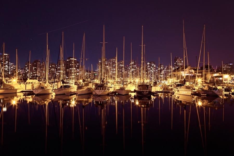 Boats docked along False Creek at night in Vancouver, BC